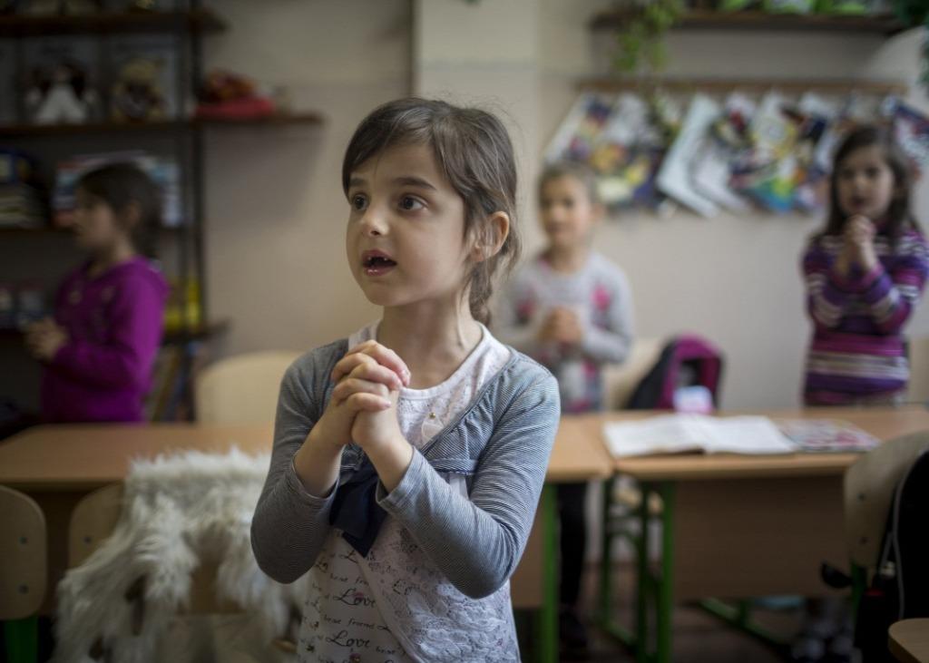 Gyerekek hittanórán a kárpátaljai Beregszászon. Noha az iskolák fenntartása az ukrán állam feladata, ez korántsem jelent garanciát a zavartalan működésre. Fűtőanyaghiány miatt telente akár hosszabb időszakokra is bezárhatnak egy-egy intézményt | Fotó: MTI/Mohai Balázs