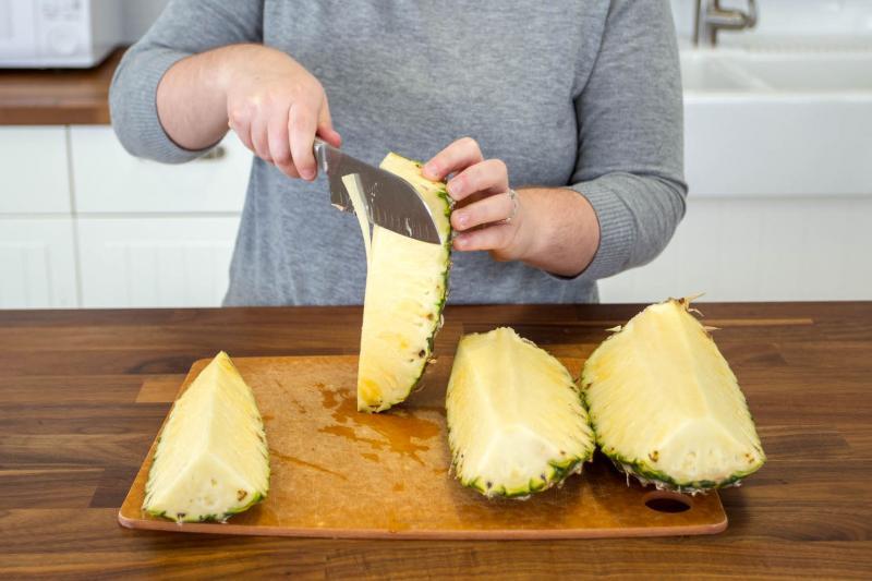 Fentről lefelé haladva negyedeljük fel az ananászt, majd vágjuk le a közepét.