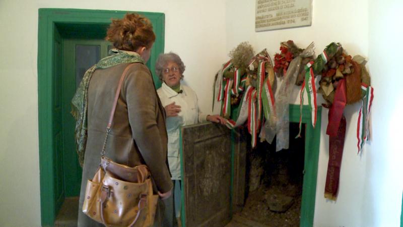Az egykori Bossányi kúria kandallósszobájában Csorba Teréz kinyitja a tűzteret elzáró ajtót, megmutatva, hogy hogyan működött régen a fűtés