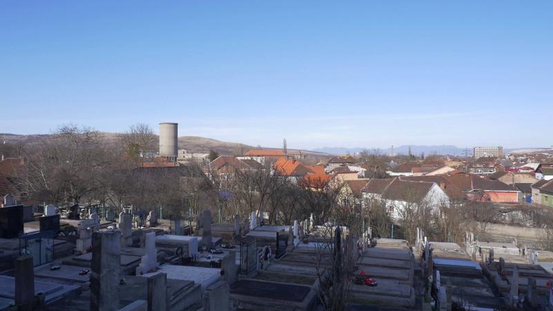 A református templom sírkertje és a város mai látképe. Az egykor számtalan kémény közül ma már csak a hűtőtorony magasodik föl.