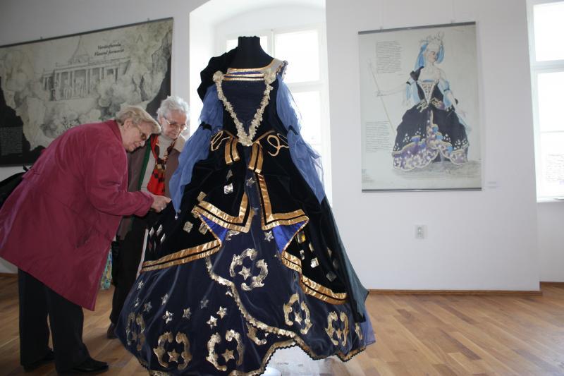 Bánffy Miklós jelmeztervezőként is kiemelkedőt alkotott. Háttérben az általa rajzolt terv, előtérben a rekonstruált kosztüm a Varázsfuvola Éj Királynőjéhez.