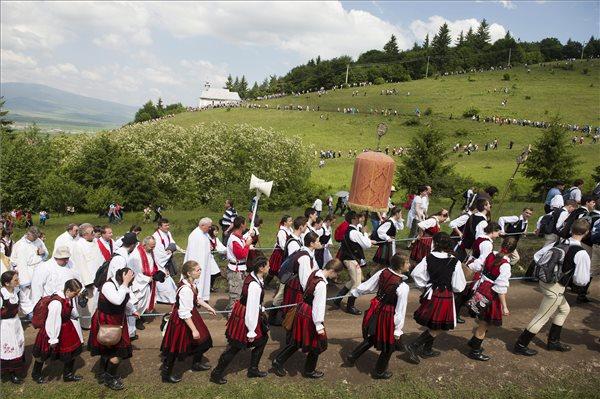 A Kis- és Nagysomlyó-hegy közötti nyeregben felállított oltárhoz érkező zarándokokCsíksomlyón 2014. június 7-én. Középen a labarum, acsíksomlyói búcsú legfőbb jelvénye. MTI Fotó: Koszticsák Szilárd